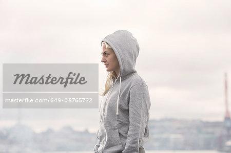 Female runner in grey hoody on misty dockside