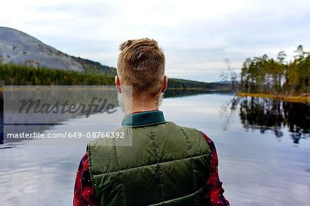 Hiker looking out at lake, Kesankijarvi, Lapland, Finland
