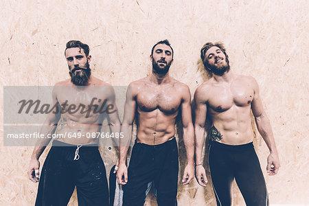 Portrait of three macho male cross trainers in gym