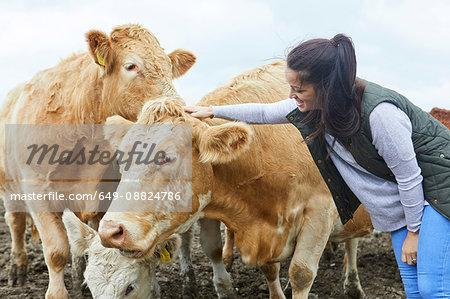 Woman on farm stroking cow