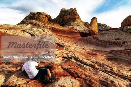 Photographer photographing White Pocket rock formation, Page, Arizona, USA