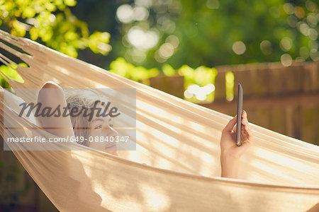 Teenage boy reclining in garden hammock browsing digital tablet