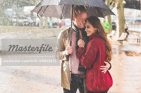 Couple with umbrella, standing under rain in park, London, UK