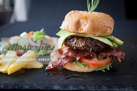 Hamburger with avocado, side salad and chips on slate