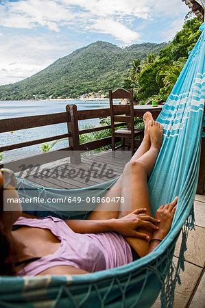Woman relaxing in a hammock, Ilha Grande, Rio de Janeiro, Brazil