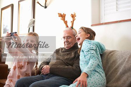 Sisters taking smartphone selfie of sleeping grandfather in reindeer antlers