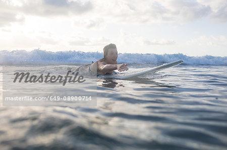 Woman paddling on surfboard in sea, Nosara, Guanacaste Province, Costa Rica