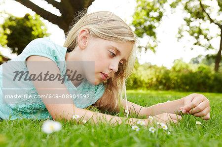Girl lying on grass gazing at daisy