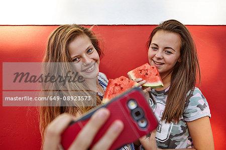 Teenage girls taking selfie and eating watermelon