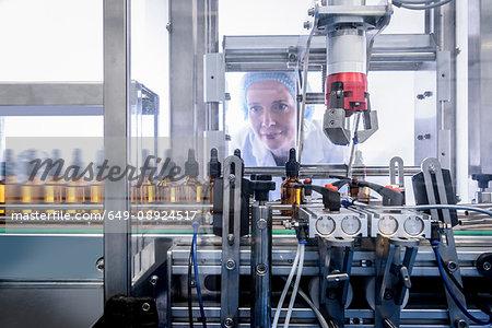 Worker inspecting bottles in pharmaceutical factory