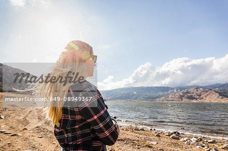Woman with flyaway long blond hair looking out at Lake Isabella, California, USA