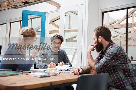 Female and male designers brainstorming at design studio desk meeting