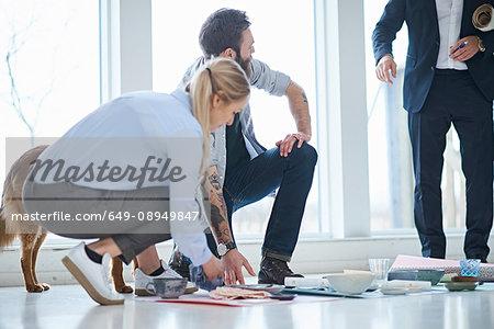 Interior design team arranging ceramics and textiles on design studio floor