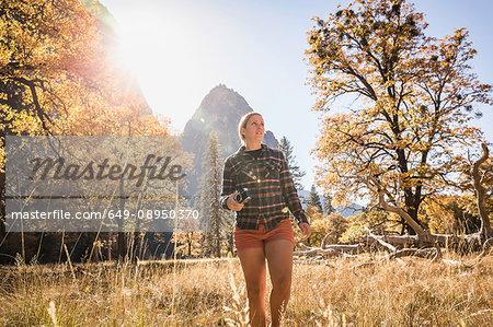 Woman with camera in autumn landscape, Yosemite National Park, California, USA