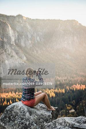 Woman sitting on boulder looking out through binoculars, Yosemite National Park, California, USA