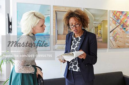 Female designer explaining blueprint to female client in office lobby