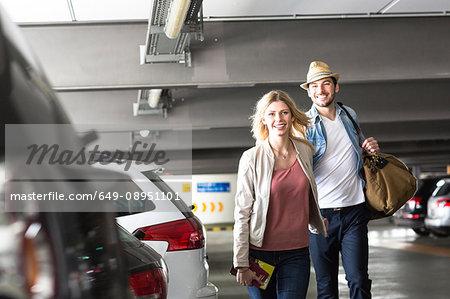 Young couple walking through airport carpark