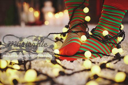 Feet of woman wearing stripy socks tangled in fairy lights
