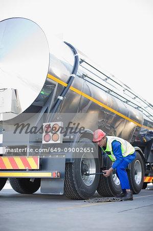 Worker changing tanker truck wheel