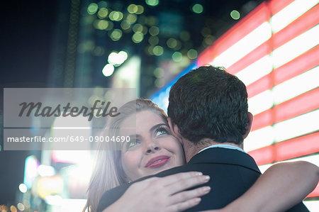 Neon american flag and young couple hugging, New York City, USA