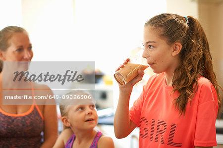 Teenage girl drinking glass of fresh smoothie in kitchen