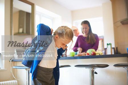 Schoolgirl putting on school satchel in kitchen