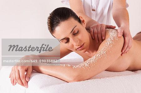 Woman in spa environment, having salt crystal massage