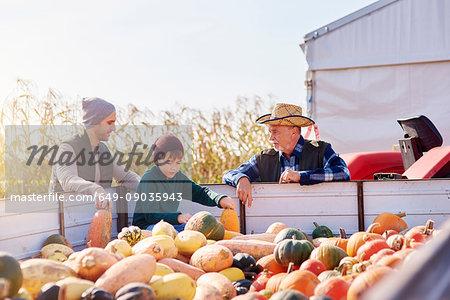 Farmers and boy at pumpkin farm
