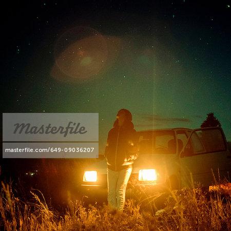 Woman in rural setting at night, leaning against car, headlights illuminated, Ural, Sverdlovsk, Russia, Europe