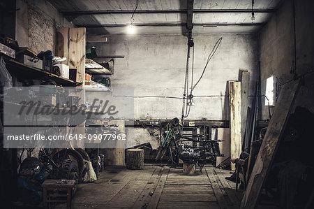 Mechanic sitting in armchair looking at dismantled vintage motorcycle in workshop