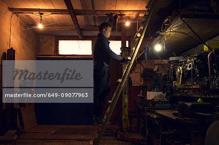 Mechanic on ladder looking at shelves in workshop