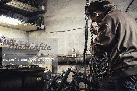 Mechanic hoisting dismantled vintage motorcycle in workshop