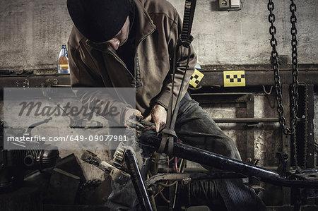 Mechanic repairing dismantled vintage motorcycle in workshop