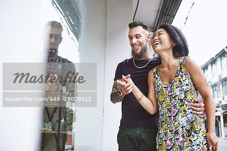 Multi ethnic hipster couple window shopping, Shanghai French Concession, Shanghai, China