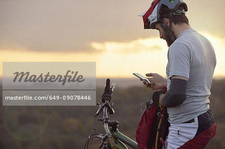 Male mountain biker looking at smartphone moorland