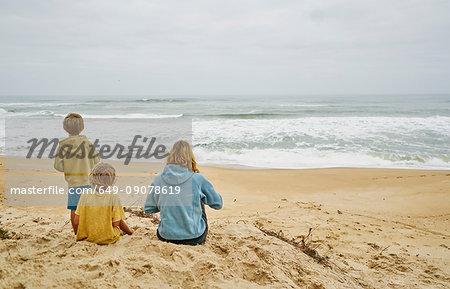 Family on beach looking away at sea, Florianopolis, Santa Catarina, Brazil, South America