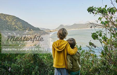 Boys on cliff looking away at beach, Florianopolis, Santa Catarina, Brazil, South America