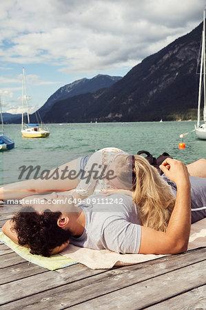 Couple lying together on pier, Innsbruck, Tirol, Austria, Europe