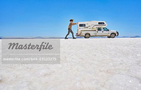 False perspective image of boy on salt flats, pretending to push recreational vehicle, vehicle in background, Salar de Uyuni, Uyuni, Oruro, Bolivia, South America