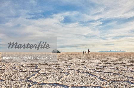 Mother and sons walking across salt flats, recreational vehicle in background, Salar de Uyuni, Uyuni, Oruro, Bolivia, South America