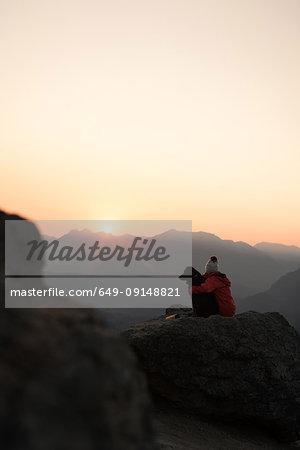 Woman with dog on hilltop at sunrise, Rattlesnake Ledge, Washington, USA