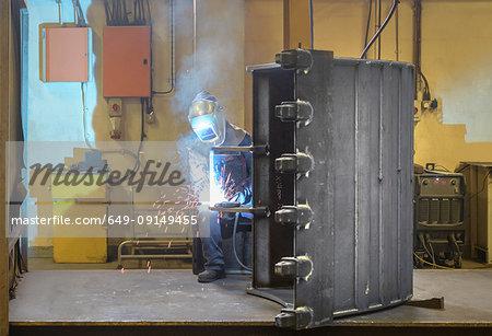 Welder welding part of digger bucket in engineering factory