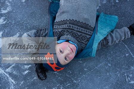 Boy lying on frozen lake, portrait