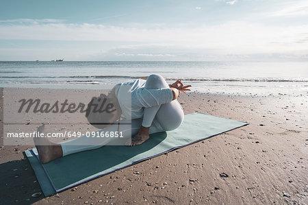 Woman practising yoga on beach