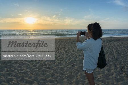 Woman taking photograph of sunset on beach