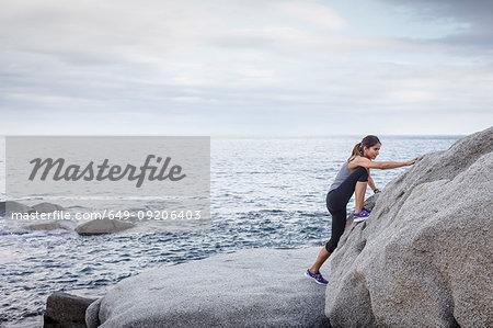 Woman scaling rock face