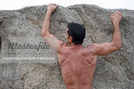 Man scaling steep rock face
