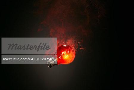 Still life of red smoking illuminated lightbulb