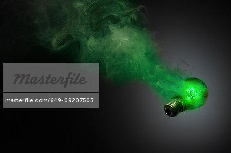 Still life of green smoking illuminated lightbulb