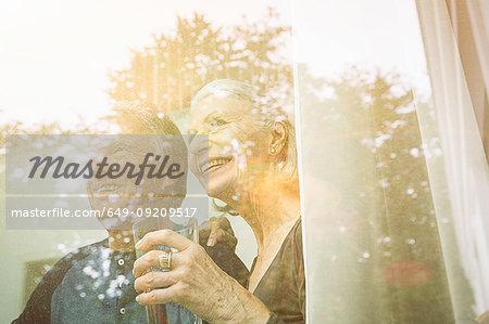 View through window of senior couple holding tumbler looking away smiling